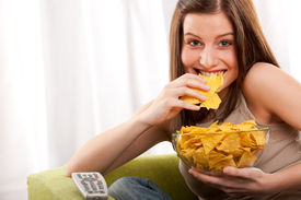 picture of potato chips  - Young woman eating potato chips in front of TV - JPG