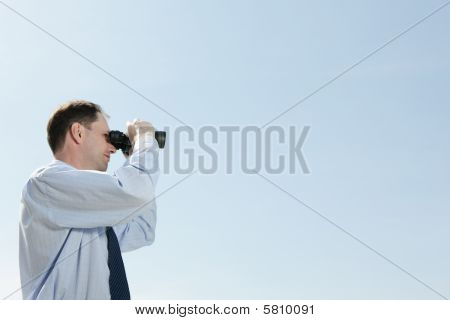Businessman With Binoculars Against Blue Sky