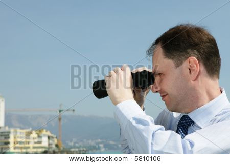 Businessman With Binoculars Looking Backward