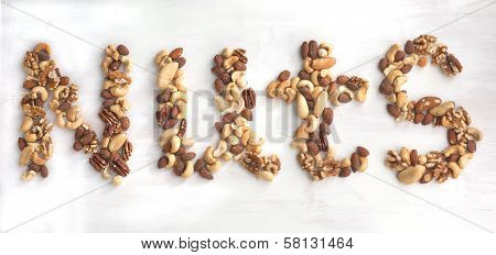 Nuts Word From Different Nuts. Mixed Nuts - Hazelnuts, Walnuts, Almonds, Cashews, Brazil Nuts And Pe