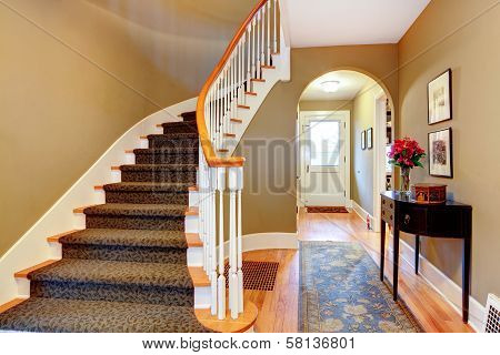Bright Hallway With Wood Stairs And Archway