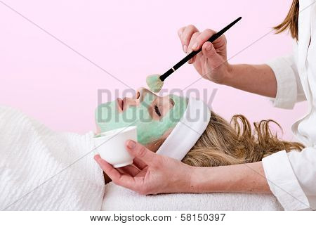 Beautician Brushing Green Facial Mask On A Woman.