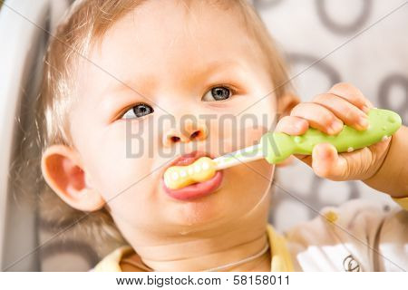 Portrait Of Baby Girl Cleaning Teeth With Toothbrush