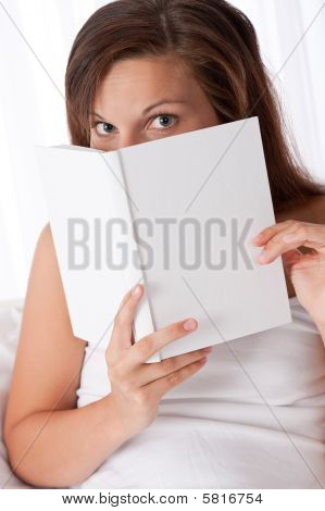 Woman Peeking Over White Book