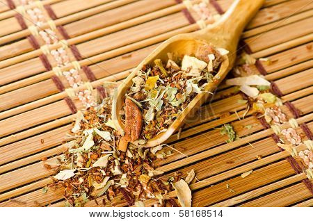 Wooden spoon with leaves of herbal tea