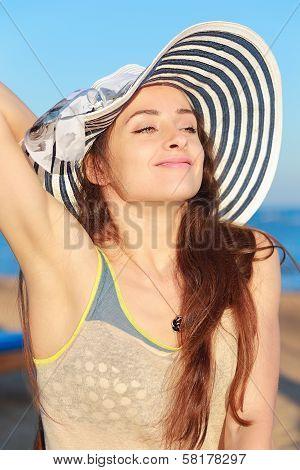 Beautiful Woman In Hat Enjoying On The Beach Under Blue Sky And Sea Background