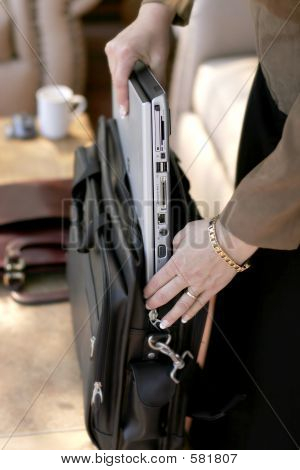 Businesswoman Packing/Unpacking Laptop