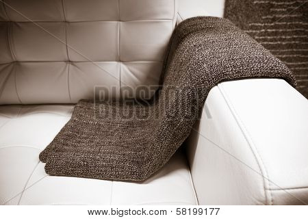 Gray Blanket Draped Over A Leather Couch