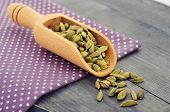 image of cardamom  - Dry cardamom seeds in scoop closeup on wooden background - JPG