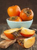 Fresh Ripe Persimmons On A Wooden Table. Selective Focus