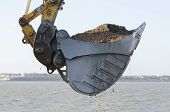 stock photo of sand gravel  - Excavator bucket dredging sand and gravel from the seafront - JPG