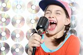 picture of rap-girl  - The girl singing karaoke wearing a baseball cap and orange shirt against the wall cd - JPG