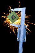 picture of microprocessor  - microprocessor clamped in a caliper with sparks on a background - JPG