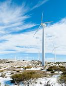pic of dynamo  - Wind turbines isolated on blue background of sky and snow around  - JPG