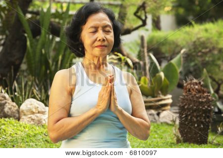 Asian Senior Woman Meditating For Yoga Outside