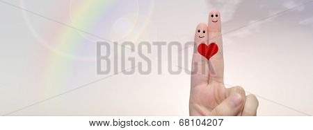 Concept or conceptual human or female hands with two fingers painted with a red heart and smiley faces over rainbow sky banner background