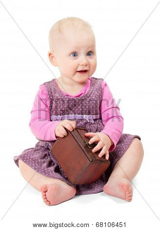 Little girl in violet dress sits and holds chest