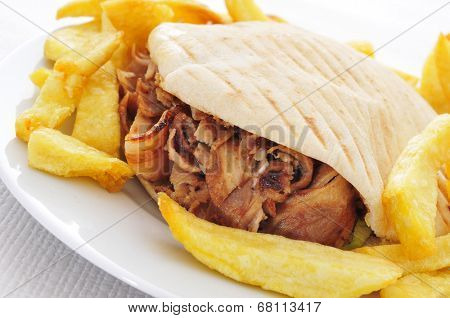 a doner kebab in a plate with french fries on a set table