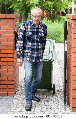 Elderly Man Pulling A Wheeled Dumpster