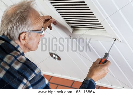 Man Tightening The Bolts On Ventilation Grille
