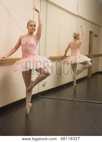 Beautiful ballerina standing en pointe with the barre in the dance studio