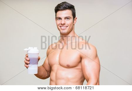 Close-up portrait of a sporty young man with protein drink over white background