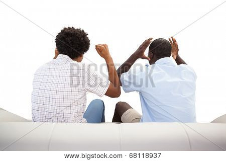 Rival sports fans sitting on the couch on white background