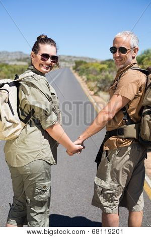 Hitch hiking couple holding hands on the road smiling at camera on a sunny day