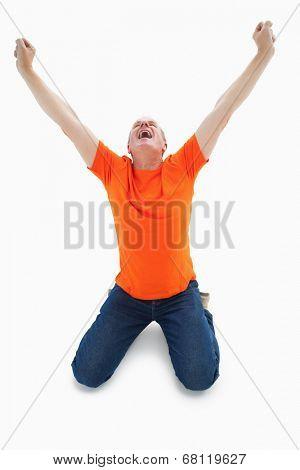 Mature man in orange tshirt cheering while kneeling on white background