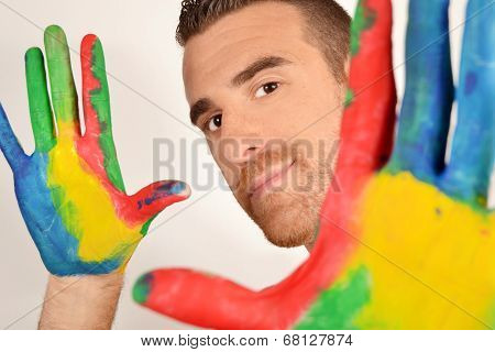 Man looking into the camera with painted hands
