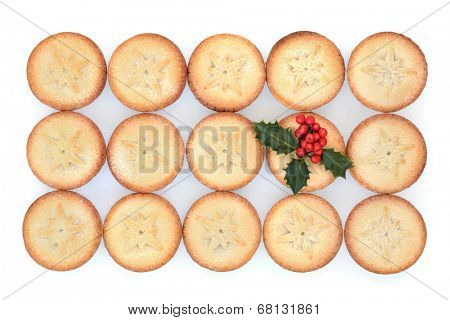 Christmas mince pie cakes and holly over white background.