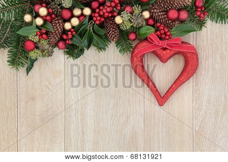 Christmas background border with red heart decoration, holly, baubles, mistletoe and winter greenery over light oak background.