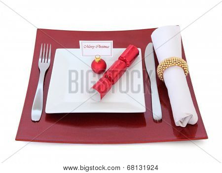 Christmas dinner place setting with plate and name tag on red bauble, cutlery, cracker and serviette with gold ring over white background.