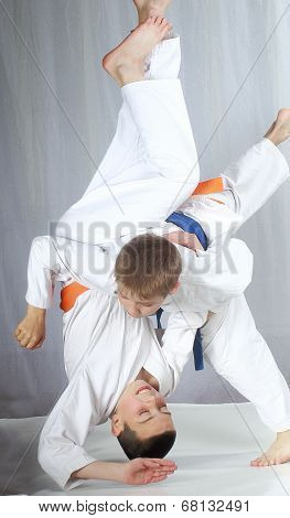An athlete with a blue belt performs technique nage-waza