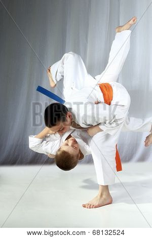 Young athlete with an orange belt performs technique nage-waza