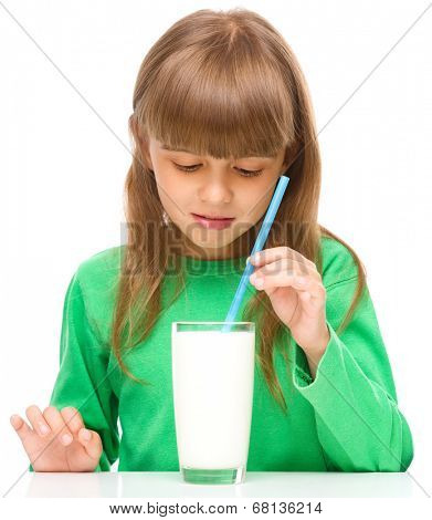 Gloomy little girl does not want to drink milk, isolated over white