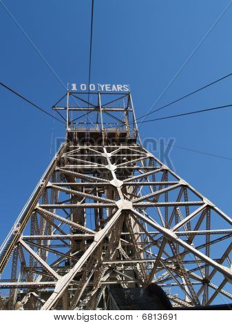 "Steel pylon towering skyward with ""100 years"" sign on top."