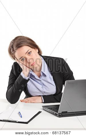 Sad businesswoman sitting at a table isolated on white background