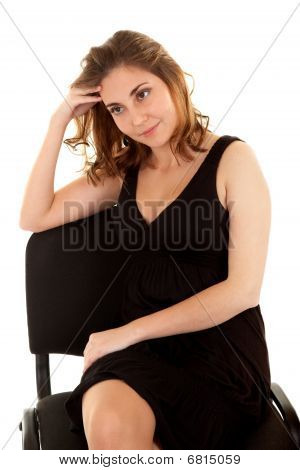 Thinking Woman In A Black Dress On A Chair