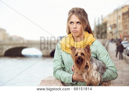 Sad girl with little dog on the bank of the river after conflict with her friend.