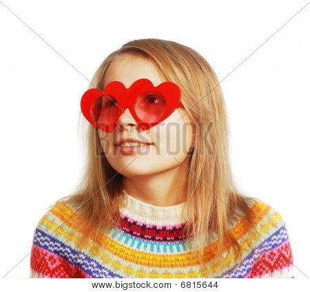 Cute girl with red heart-shaped glasses on white