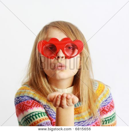 Cute girl with red heart-shaped glasses blowing kiss