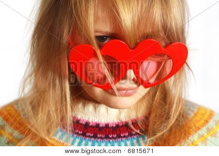 Cute girl with red heart-shaped glasses
