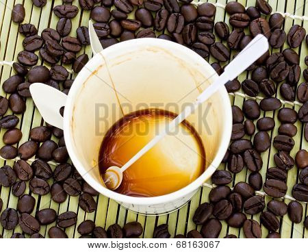 Paper Cup Of Black Coffee And Coffee Bean On Bamboo Straw