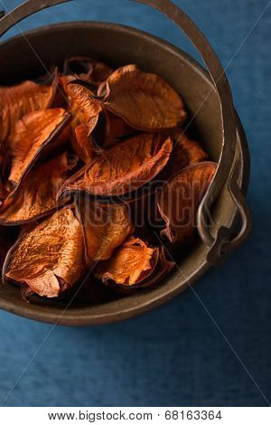 Aromatic, dried orange potpourri leaves  in copper bowl