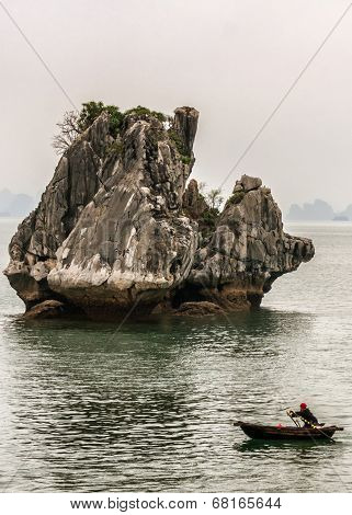 Lone Rowboat Travels In Front Of Spectacular Limestone Rock.