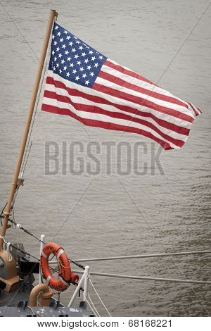 NEW YORK - MAY 22: The American flag flies from the stern of the Famous-class cutter USCGC Campbell (WMEC 909) moored at Pier 92 for Fleet Week NY on May 22, 2014.