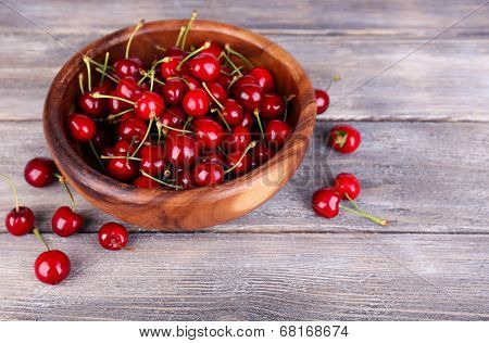 Ripe sweet cherries in bowl on wooden table