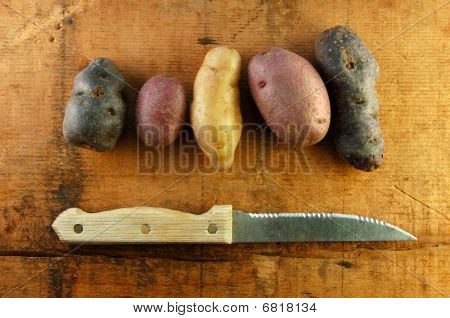 Variety Of Fingerling Potatoes On Wooden Table