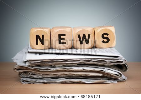 Newspapers folded and stacked with the word news in wooden block puzzle dice concept for newspaper, the media, press release and global communications